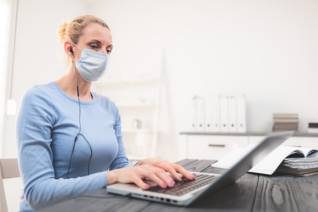 Online teacher with a protective mask tutoring over the internet.